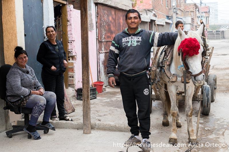 hombre junto a su caballo blanco enganchado a la taliga y dos mujeres a la izquierda una sentada y la otra de pie sonrientes en la mahala de los gitanos de bulgaria
