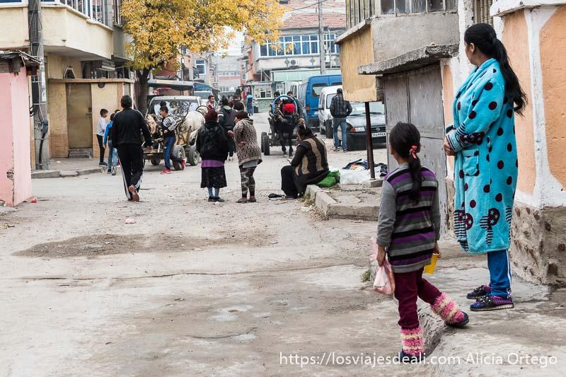 vista de una calle del barrio con una mujer con bata de color azul eléctrico con topos negros y niña a su lado mirando a unas taligas que hay al fondo