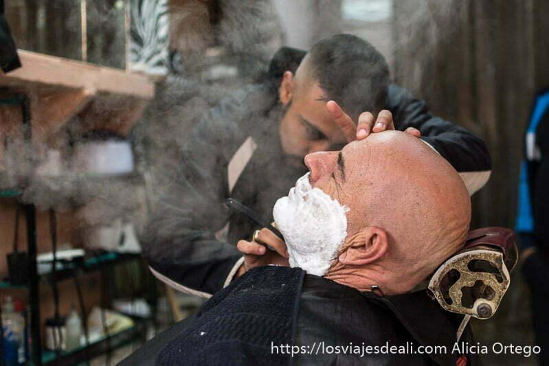 hombre afeitándose en el barbero con vapor delante de la cara para abrir los poros