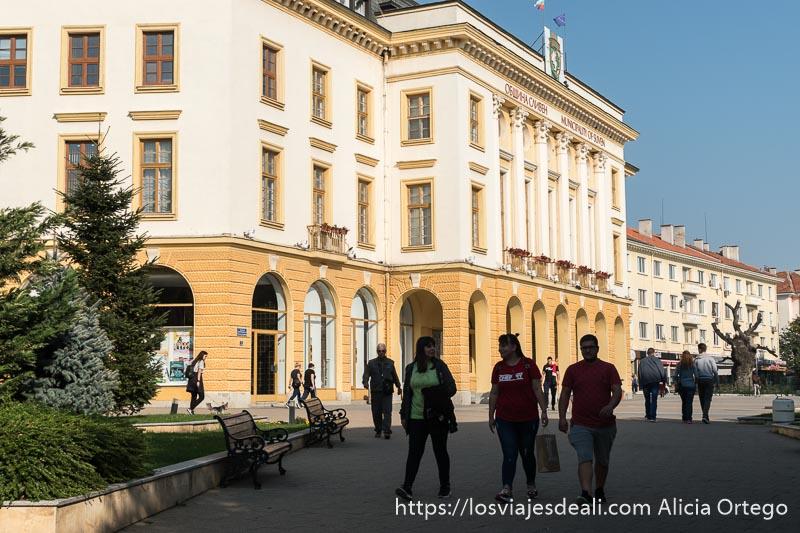 gente paseando por el centro de sliven con edificios neoclásicos pintados de colores en un día muy soleado