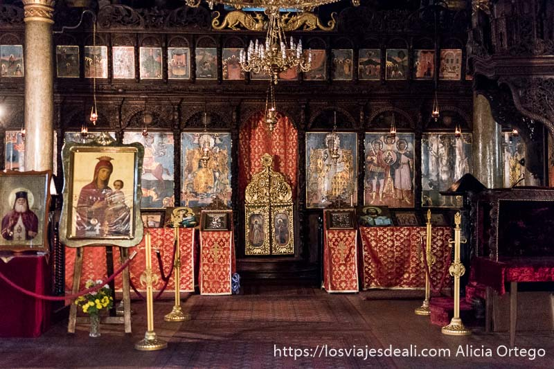 interior de iglesia de sliven con muchos cuadros de santos y la virgen maría y lámpara tipo araña dorada