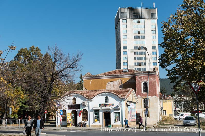 edificio antiguo en el centro de sliven y detrás una torre tipo soviética
