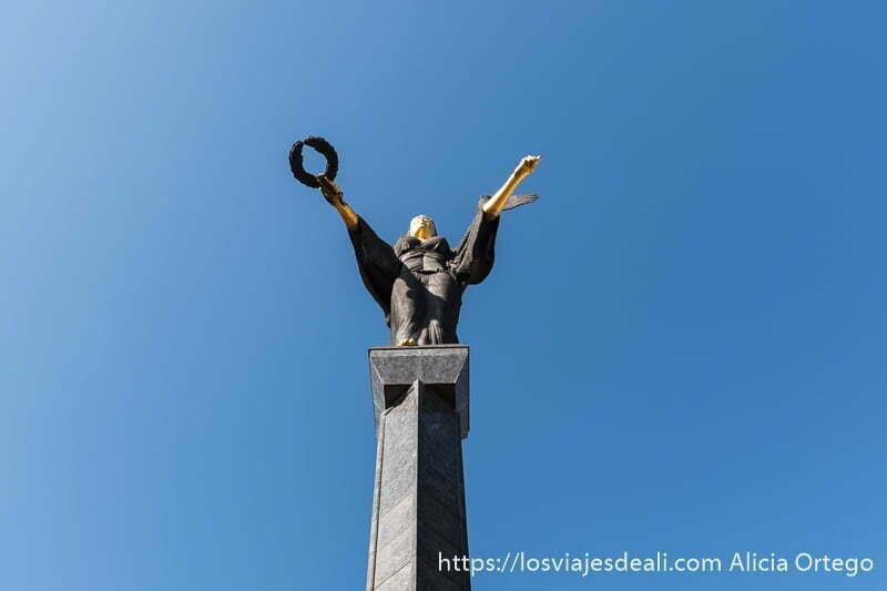 estatua de sofía con brazos extendidos pintados de oro en una mano lleva una corona de laurel