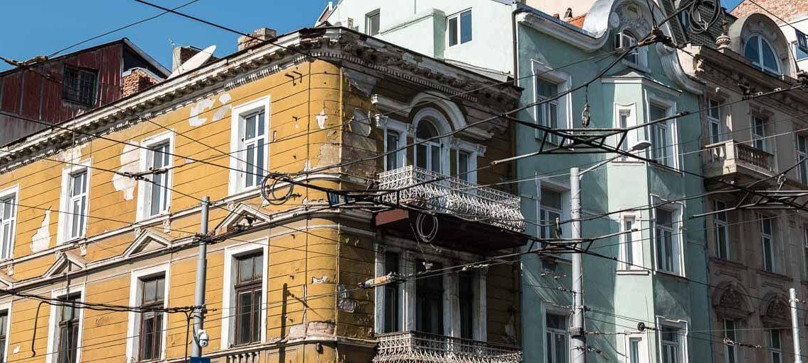 esquina de edificios antiguos pintados de color amarillo y verde desconchados con cables de tranvía en sofía