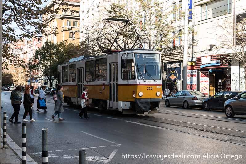 tranvía amarillo y blanco y gente cruzando la calle para subirse
