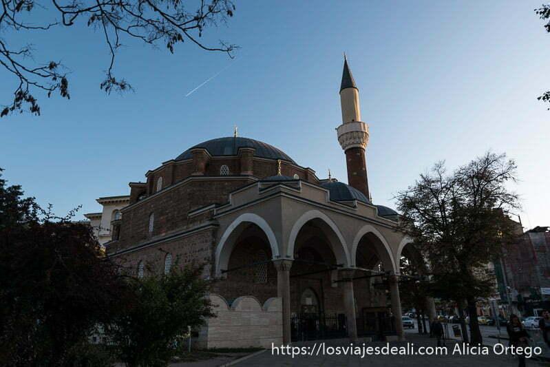 mezquita de sofía con minarete parcialmente iluminado por sol de atardecer