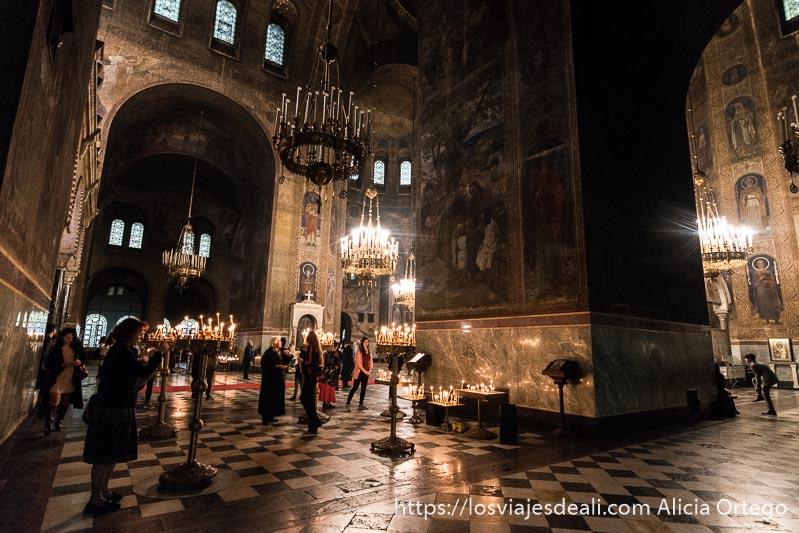 nave central de alexander nevski con gente poniendo velas en semioscuridad