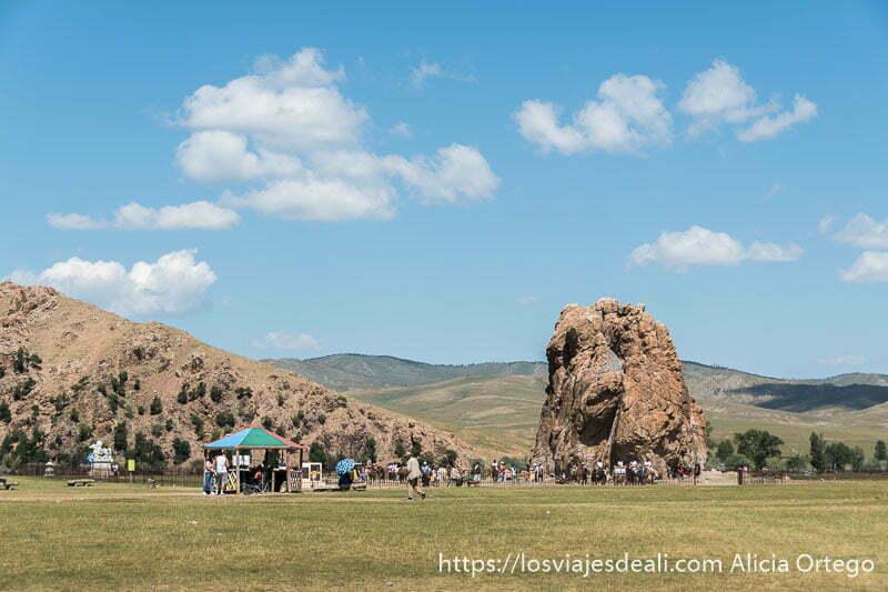 roca thaikar muy grande en medio de un prado con gente alrededor y una caseta con tejado de colores en mongolia central