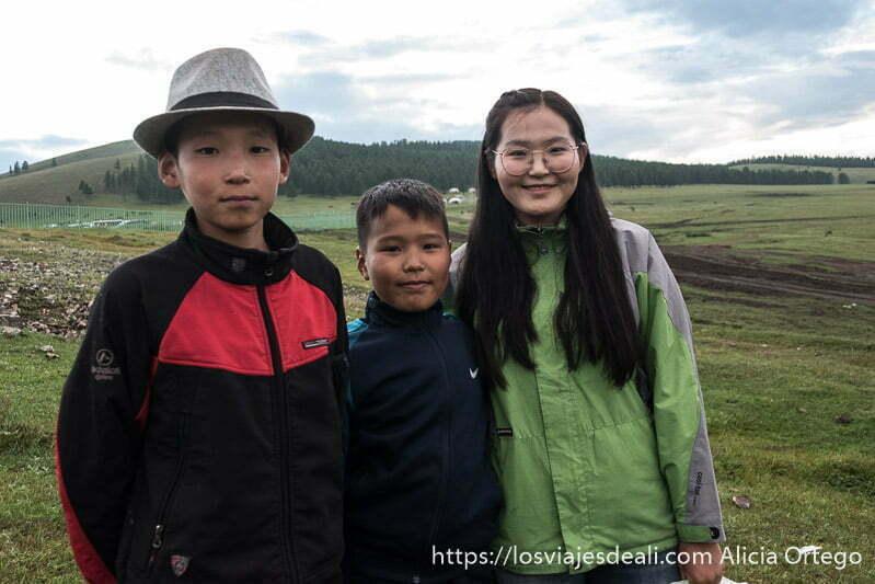una chica mongol con gafas y sus dos hermanos uno de ellos con sombrero de fieltro en el valle de tsenherin en mongolia central