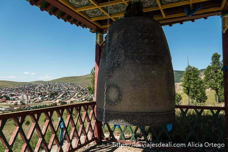 gran campana de piedra con letras chinas y al fondo la ciudad de tsenserleg en mongolia central