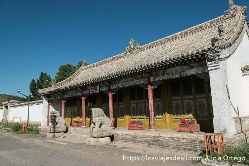 puerta principal del monasterio de tsenserleg con tejado ondulado y en la parte superior el símbolo budista de dos cervatillos y la rueda de la vida en oro