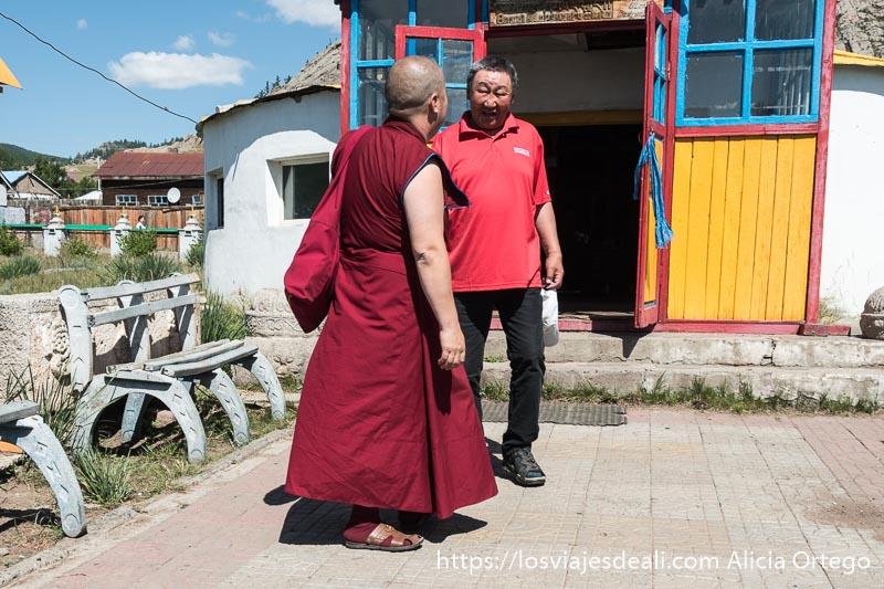 un monje budista con traje rojo hablando con un hombre en la puerta de un monasterio en mongolia central