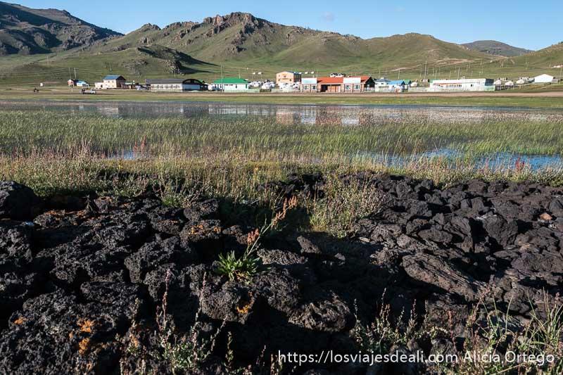 suelo de piedras volcánicas y más allá el agua y la otra orilla con algunos edificios que se reflejan en el agua