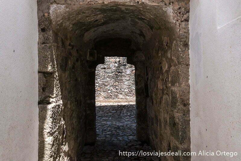 pequeño pasaje de piedra con techo abovedado que da paso a otro patio de piedra