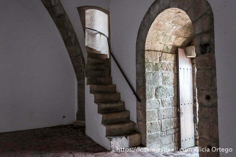 interior de torre del homenaje con paredes encaladas y escaleras de piedra y puerta de piedra con forma de arco