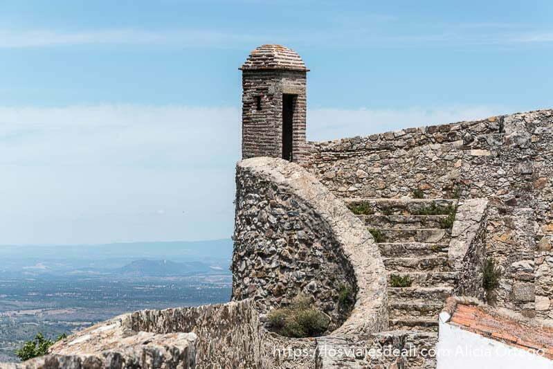 torreo de vigilancia con escaleras de acceso con forma curvada y cielo azul con nubes y paisaje detrás