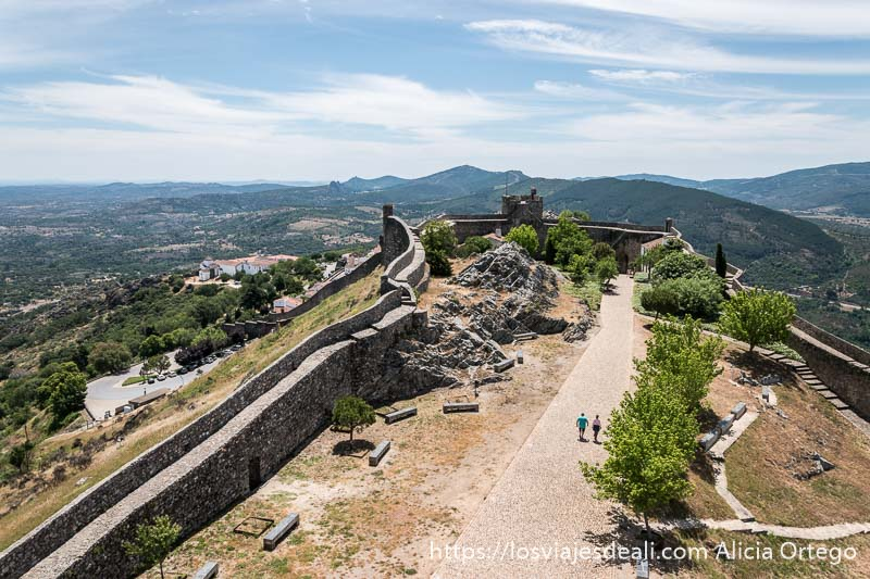 vista del patio de armas con muralla rodeándolo desde arriba y sierra al fondo en marvao