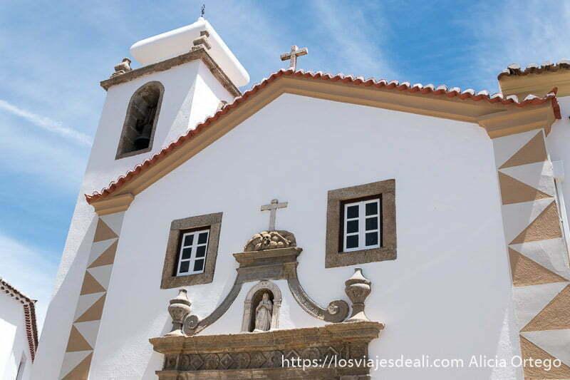 iglesia de maravao recién pintada de blanco con ventanas enmarcadas en piedra y virgen sobre la puerta