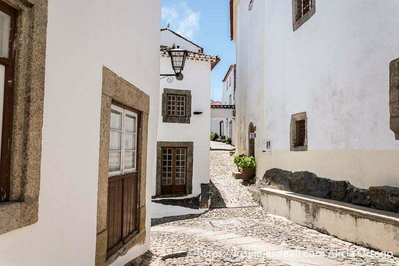 calles con casas blancas enmarcadas en piedra de granito y algunas macetas en las puertas de las casas