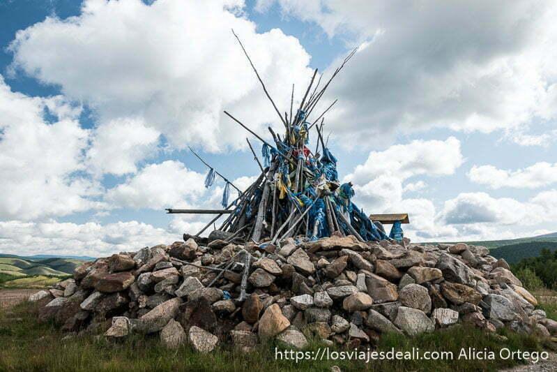 altar hecho con piedras y palos en forma de tippie con pañuelos de seda azul