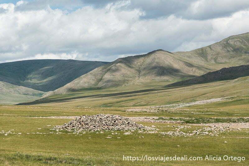 tumba neolítica con túmulo de piedras en el centro y al fondo montañas rocosas en un lugar de mongolia