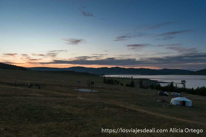 tienda ger en un prado con el lago a la derecha y cielo anaranjado en un lugar de mongolia