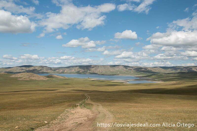 lago zuun nuur visto desde arriba con la pista que seguimos y cielo azul con nubes blancas en un lugar de mongolia