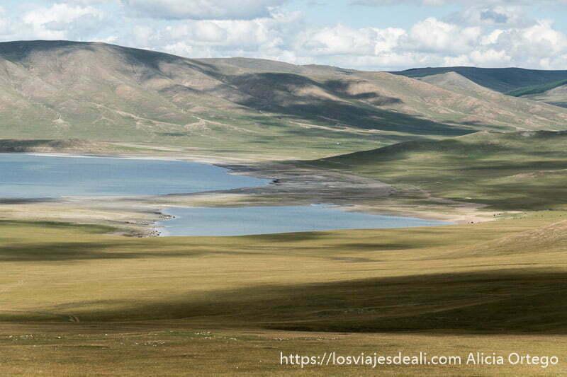 lago zuun nuur visto desde lejos rodeado de montañas rocosas y prados con la sombra de las nubes
