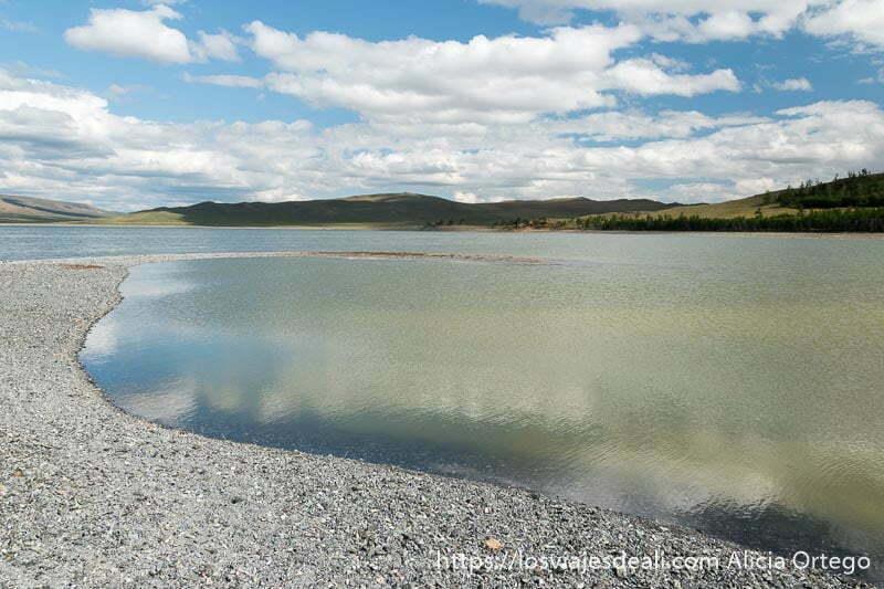 lago zuun nuur con orilla de guijarros blancos en curva y nubes reflejándose en el agua en un lugar de mongolia