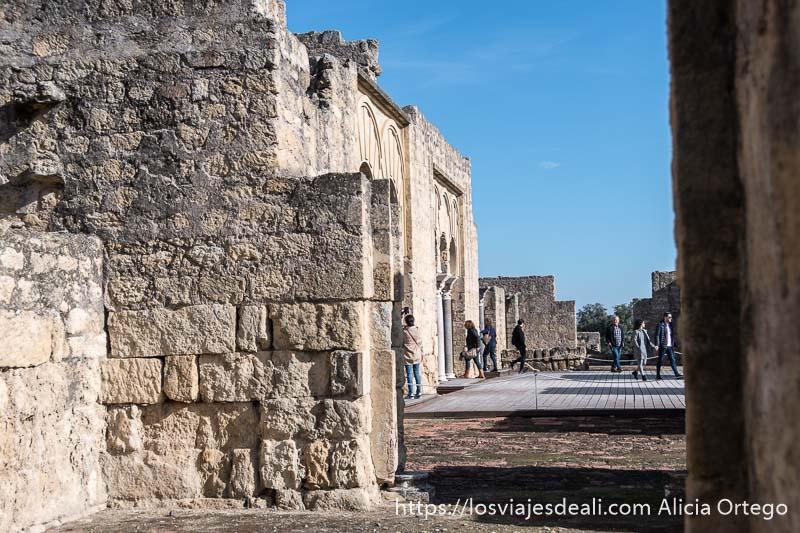 vista lateral de la portada de la basílica de medina azahara con turistas yendo y viniendo