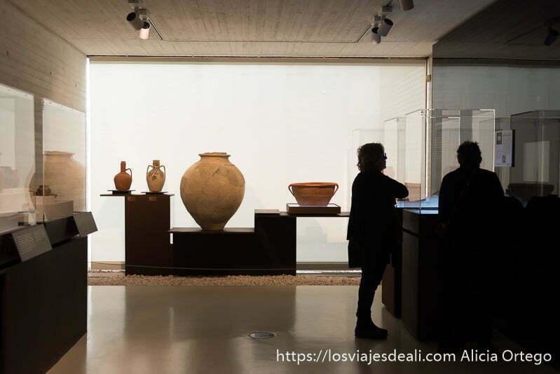 sala del museo con vasijas de barro y dos visitantes a contraluz observando una vitrina