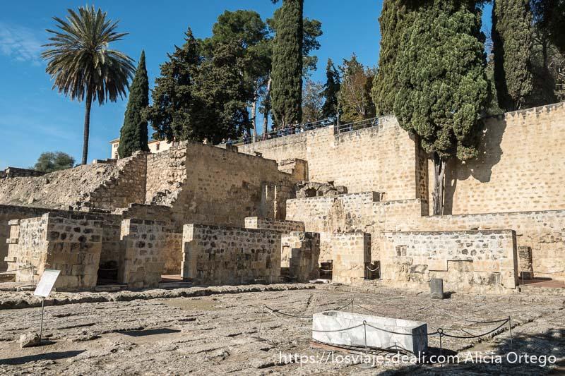 patio de casa de medina azahara rodeado de muretes con puertas y en el centro un sarcófago romano