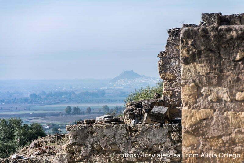muralla de piedra y al fondo el paisaje con una colina con castillo