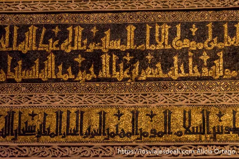 detalle de los mosaicos con letras árabes pintados de oro y fondo oscuro en el mihrab de la mezquita