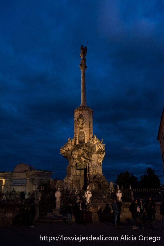 monumento Triunfo de San Rafael con columna muy alta y arriba la estatua rodeado de nubes en la hora azul visitar córdoba
