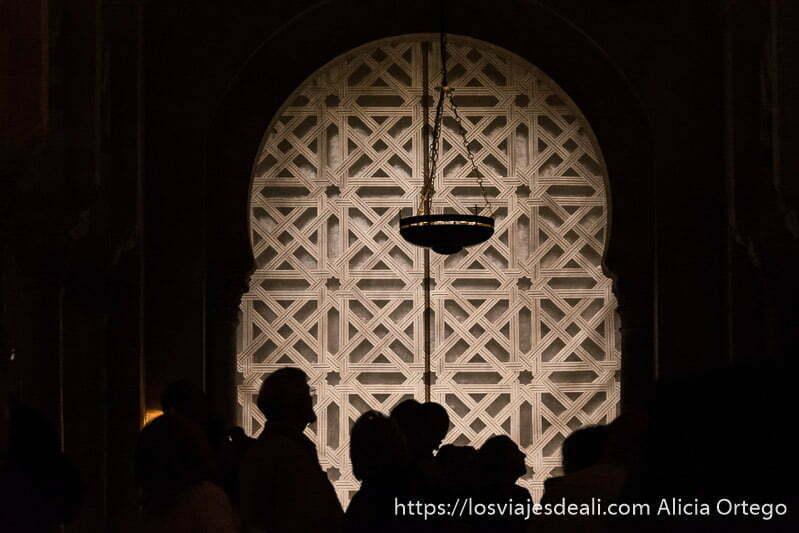 siluetas de visitantes recortándose con puerta de decoración árabe al fondo y una lámpara negra con cadenas colgando en la mezquita de córdoba