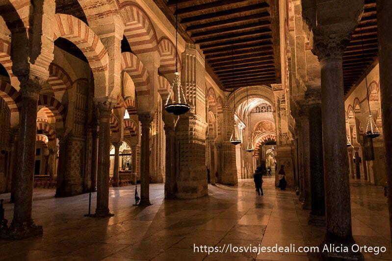 interior de la mezquita con arcos y columnas y lámparas colgando visitar córdoba