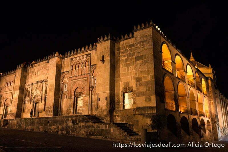 exterior de la mezquita de córdoba iluminada por la noche se ven varias puertas con arcos y puertas de hierro brillantes