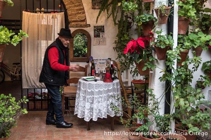 propietario de un patio junto a una mesita con mantel blanco bordado y rodeado de macetas con plantas visitar córdoba