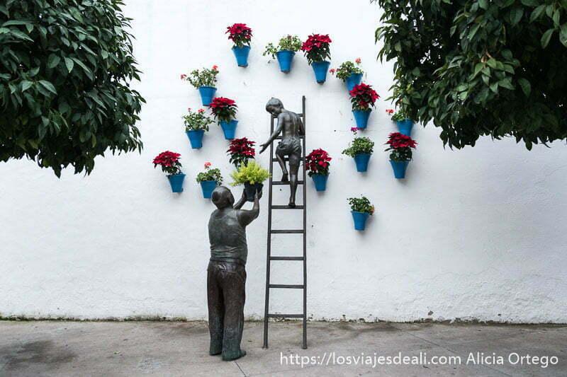 monumento a los patios en el centro histórico de córdoba donde se ve a un abuelo levantando una maceta para dársela a un niño subido a una escalera en pared blanca con macetas con flores