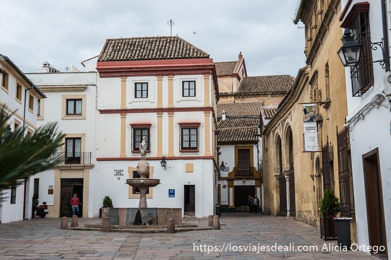 plaza del potro con fuente con estatua de un potro y casa de tres pisos pintada de blanco y amarillo visitar córdoba