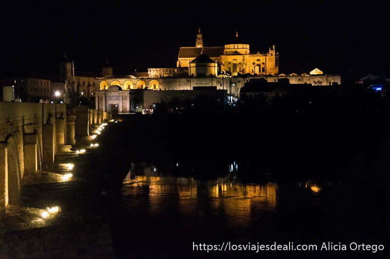 puente romano con la mezquita al fondo y su reflejo en el río por la noche, con iluminación anaranjada