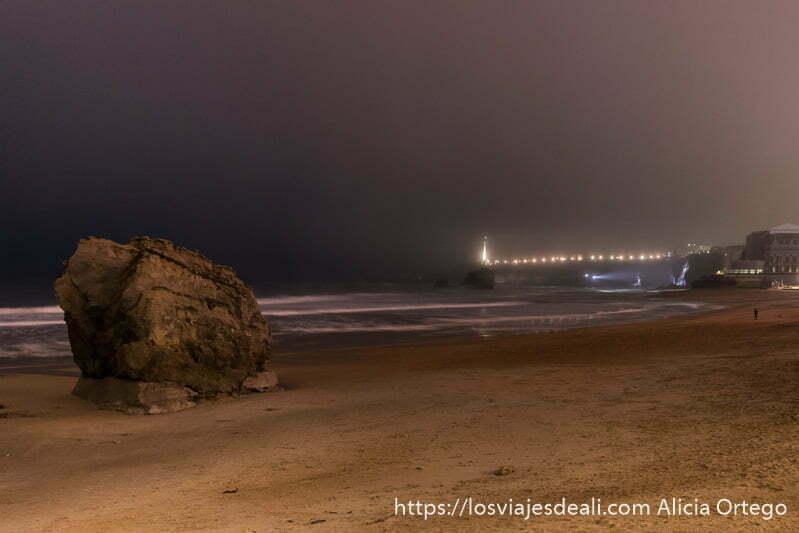 playa de noche con gran roca en la arena y el faro al fondo y mucha niebla en la excursión a san juan de luz y biarritz