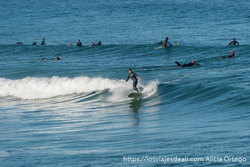 un surfista cogiendo una ola y otros detrás esperando a otra