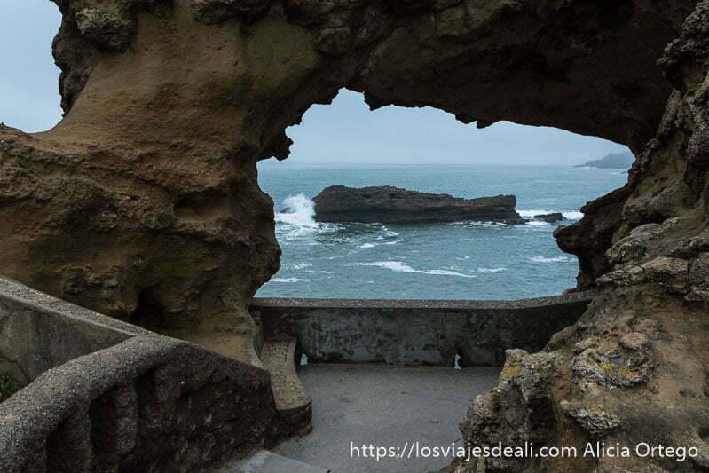 ventana de roca y al fondo el mar con otra roca contra la que choca una ola en la excursión a san juan de luz y biarritz