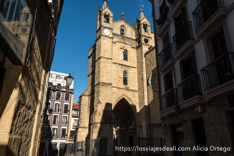 fachada de iglesia de san vicente con dos torres campanario y un reloj y un arco puntiagudo en la entrada