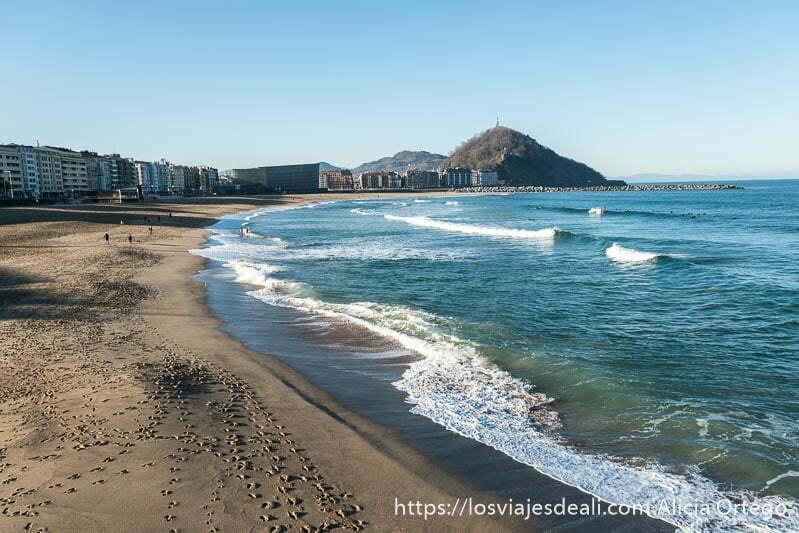 playa de zurriola es larga en forma semicircular y al fondo está la isla de santa clara