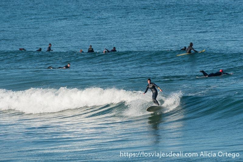surfista de pie sobre su tabla haciendo una ola y otros detrás esperando a la siguiente
