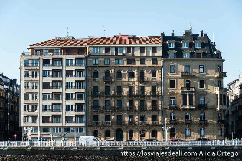 tres edificios adosados, grandes, con muchas ventanas y balcones y barandilla de hierro blanca frente a ellos