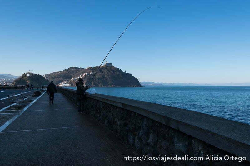 pescador con su caña en el paseo nuevo de san sebastián con el monte igueldo al fondo